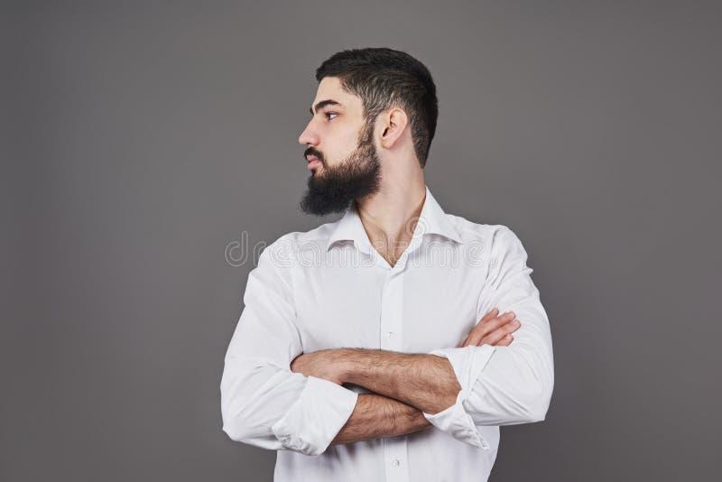 有倾斜对有横渡的胳膊的灰色墙壁的胡子的年轻英俊的人 免版税图库摄影