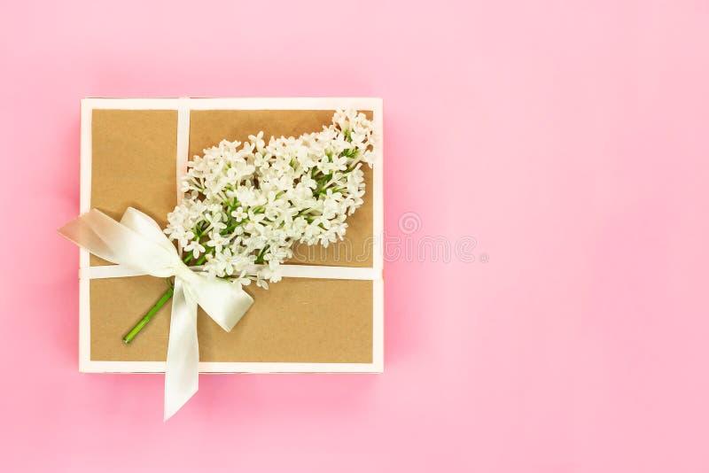 有假日弓的礼物盒和在浅粉红色的背景的白色淡紫色花和绿色叶子 r 库存照片