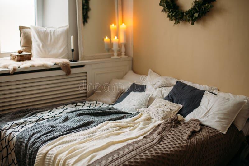 有假日装饰的明亮的舒适现代卧室 与灰色卧具集合和被编织的枕头对此,木机架的床 免版税库存图片