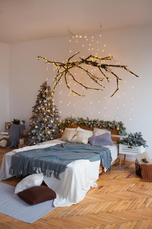 有假日装饰的白色舒适现代卧室 木床在有欢乐圣诞树的斯堪的纳维亚样式室 免版税图库摄影