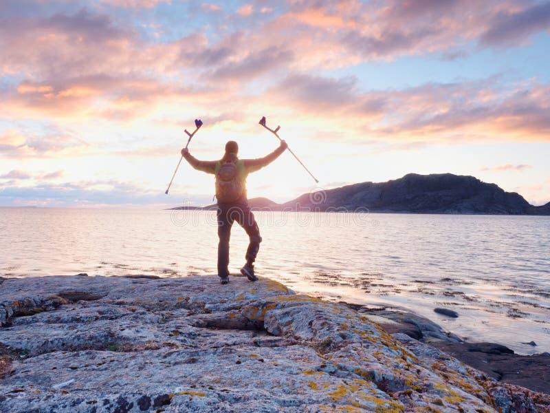 有假肢和拐杖的残疾人在海附近在天空中的握手 晚上太阳 免版税库存照片