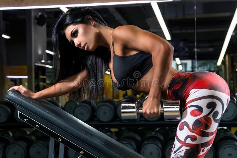 有做与后面的美好的运动身体的年轻女人锻炼由哑铃 库存照片