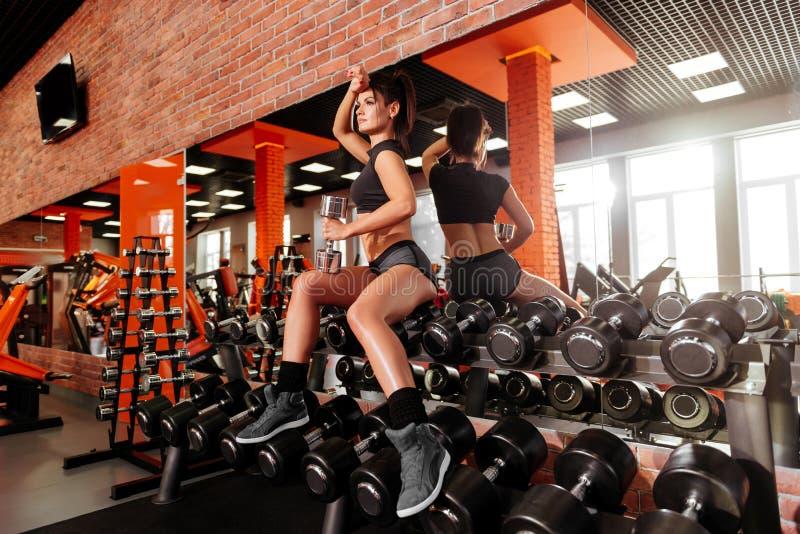 有做与哑铃的美好的身体的肌肉年轻女人锻炼 免版税库存图片