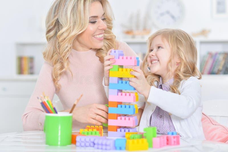 有做与建设者的小女儿的母亲图 免版税库存图片