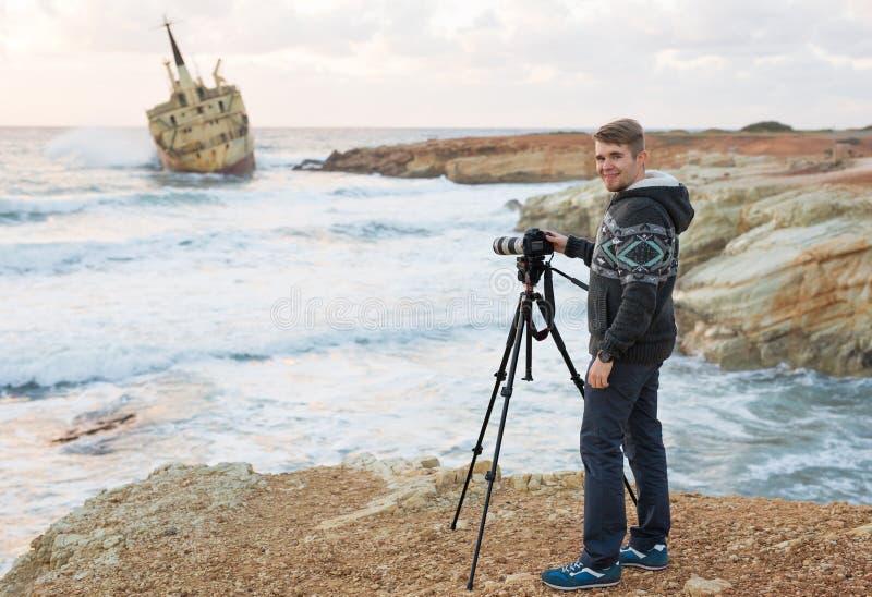 有做与照相机的背包的年轻摄影师照片海和岩石 钓鱼地中海净海运金枪鱼的偏差 免版税库存照片