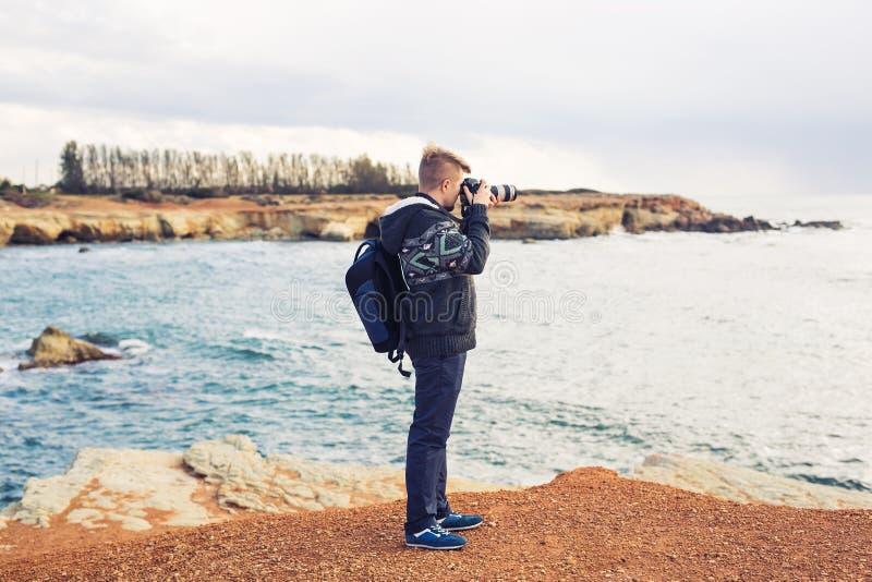 有做与照相机的背包的年轻摄影师照片海和岩石 钓鱼地中海净海运金枪鱼的偏差 免版税图库摄影