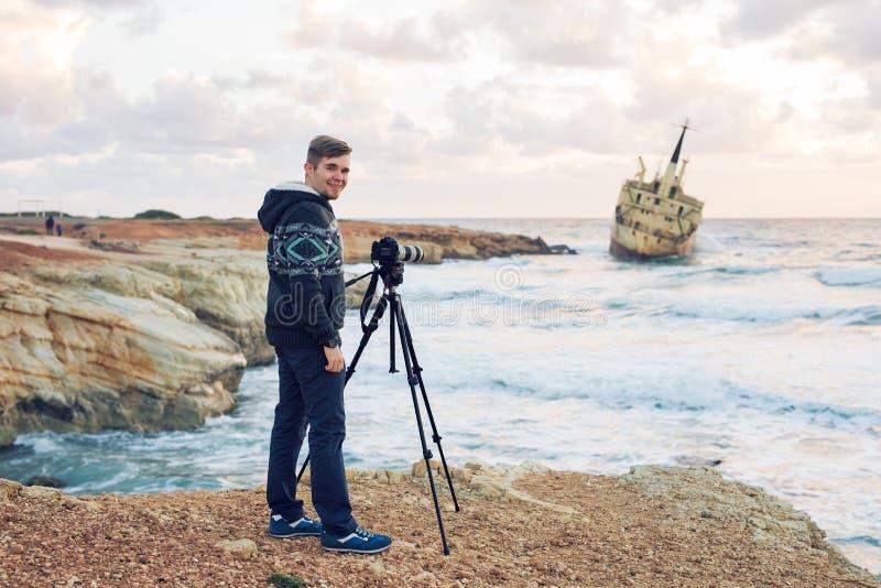 有做与照相机的背包的年轻摄影师照片海和岩石 钓鱼地中海净海运金枪鱼的偏差 免版税库存图片