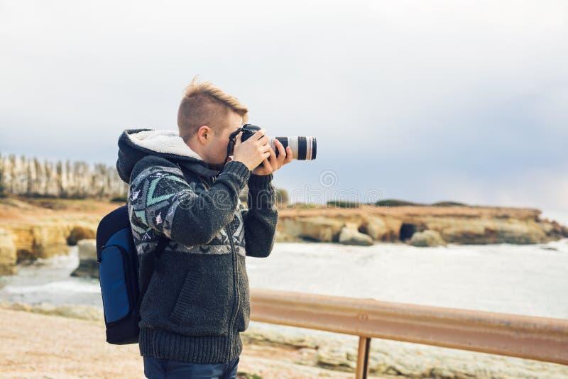 有做与照相机的背包的年轻摄影师照片海和岩石 钓鱼地中海净海运金枪鱼的偏差 库存图片
