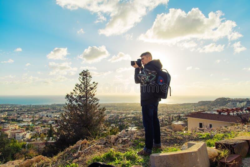有做与照相机的背包的年轻摄影师照片海和岩石 钓鱼地中海净海运金枪鱼的偏差 库存照片