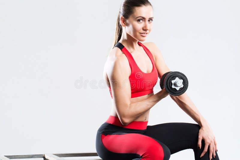 有做体育锻炼的哑铃的愉快的运动妇女,隔绝在灰色背景 库存图片