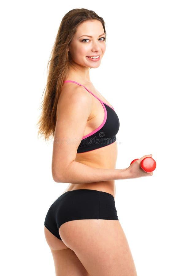 有做体育锻炼, isolat的哑铃的愉快的运动妇女 免版税库存图片