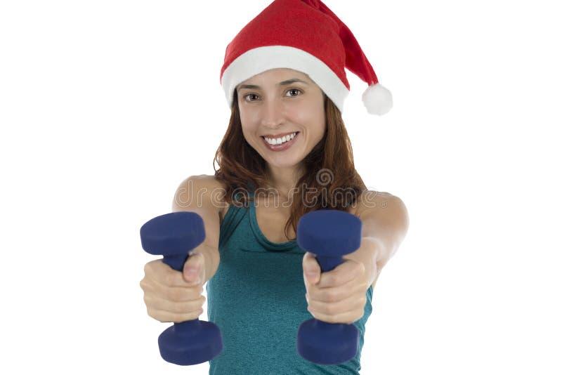 有做健身的dumbells的年轻圣诞节健身妇女 免版税库存图片