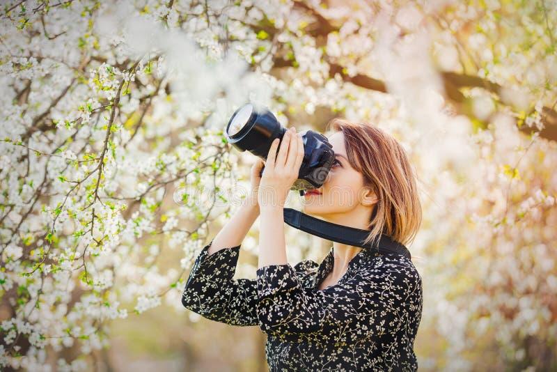 有做图象的专业照片照相机的女孩开花的树 免版税库存图片