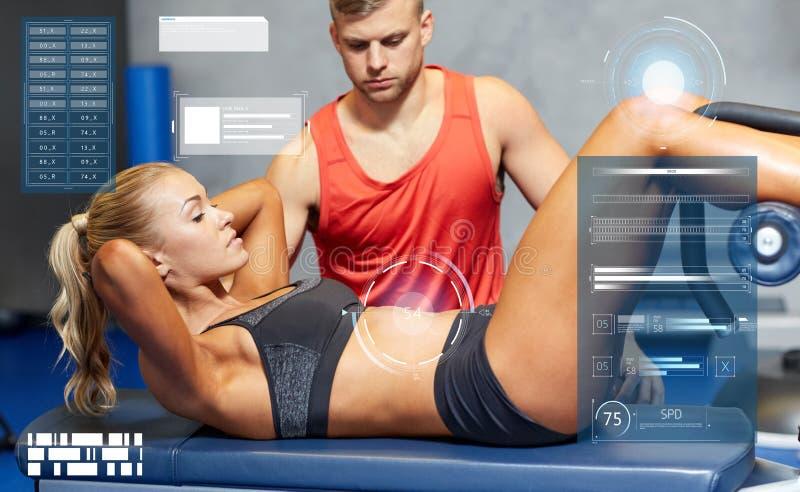 有做在健身房的个人教练员的妇女仰卧起坐 免版税库存照片