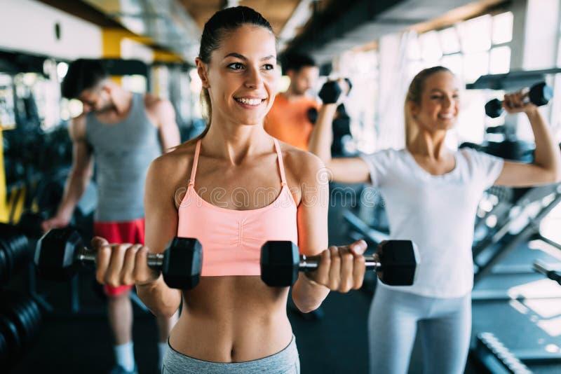 有做在健身房的朋友的年轻可爱的妇女锻炼 免版税图库摄影