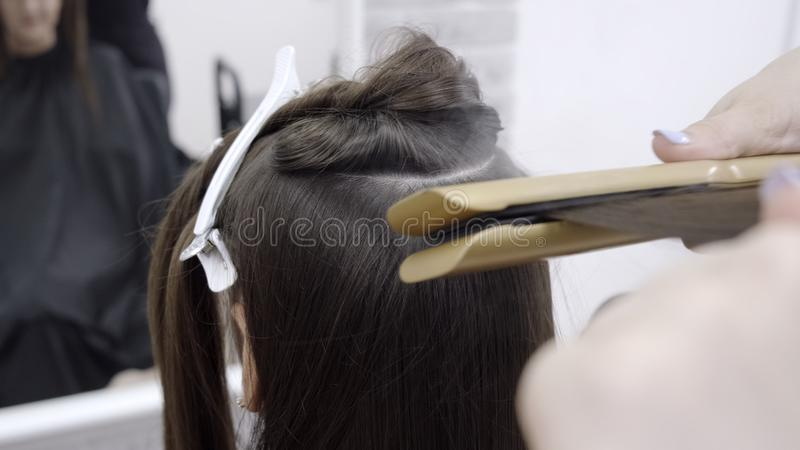 有做在发廊的长的深色的头发美发师的逗人喜爱的女孩头发分片 护发治疗的概念 库存照片