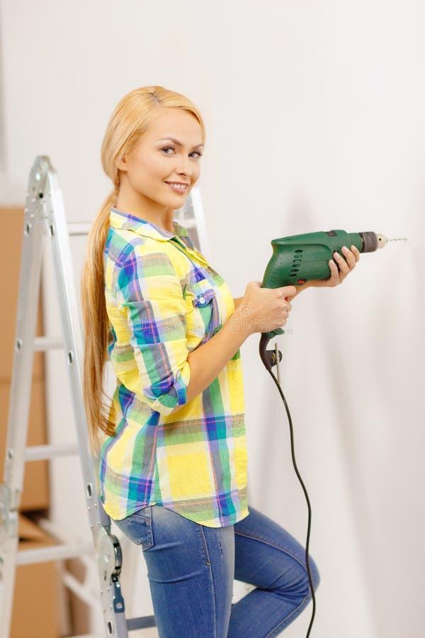 有做在墙壁的电钻的妇女孔 图库摄影