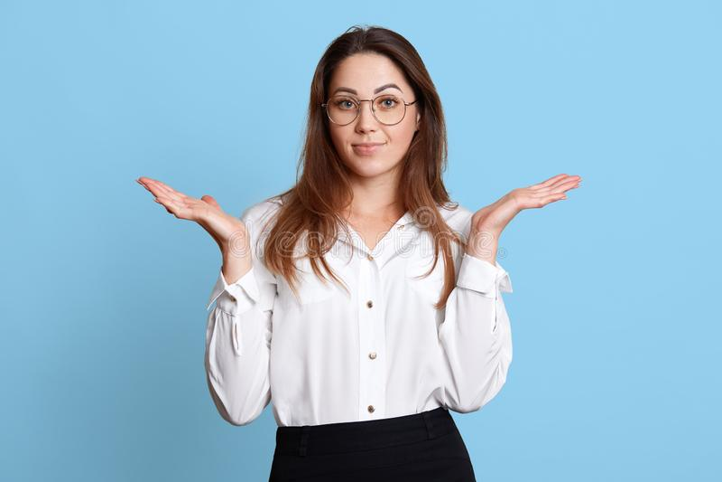 有做姿态的长发的无能为力的吸引人年轻女性,举她的手,看起来迷茫关于工作,摆在被隔绝 库存照片