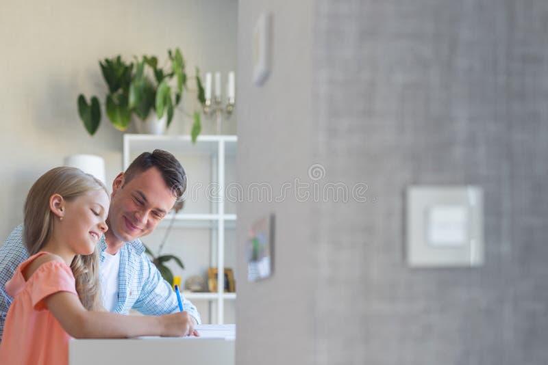 有做家庭作业的一个小女儿的年轻爸爸户内 免版税库存照片