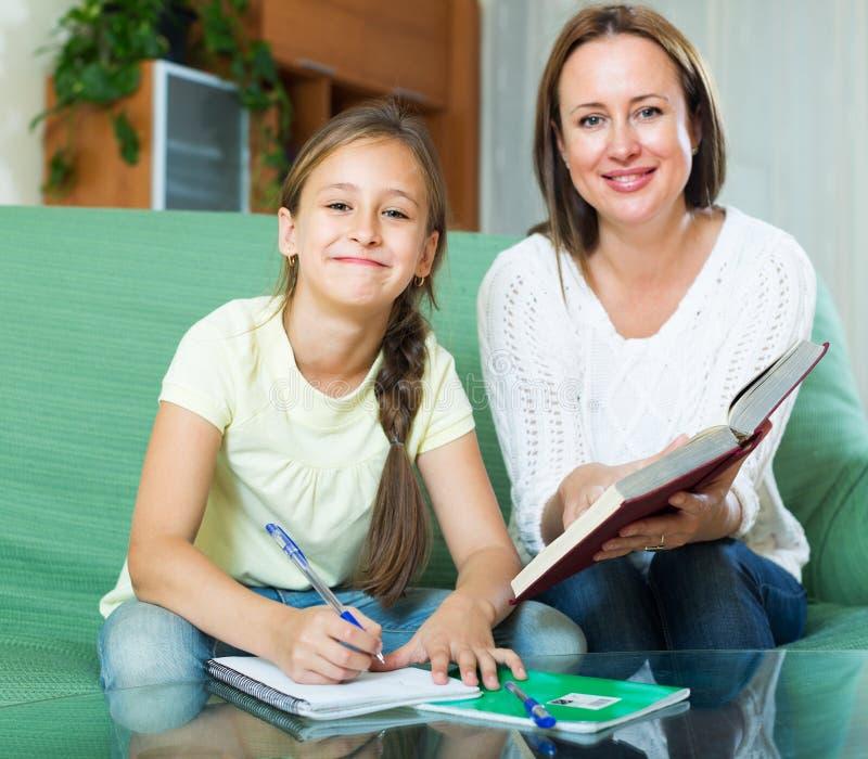 有做家庭作业的小女儿的母亲 库存照片