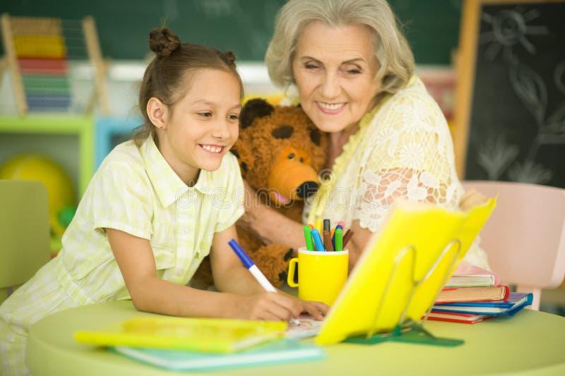 有做家庭作业的小女孩的祖母 库存照片