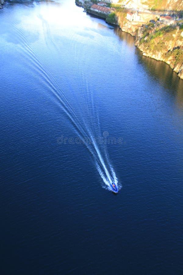 有做波浪的小船的蓝色河 免版税库存照片