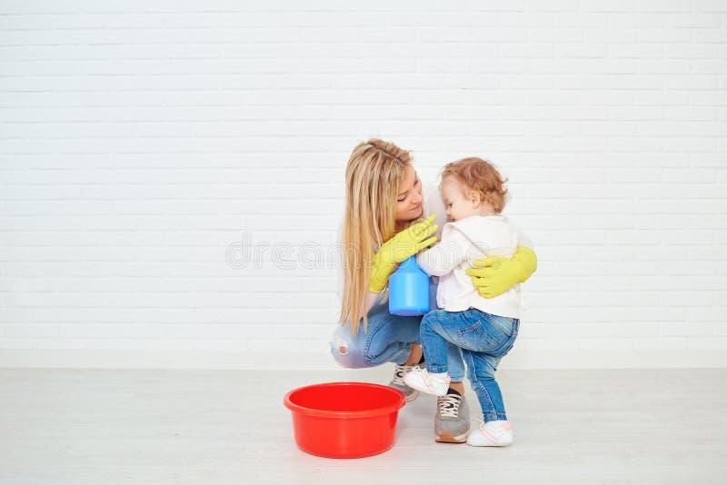 有做清洁的婴孩的母亲在屋子里 免版税图库摄影