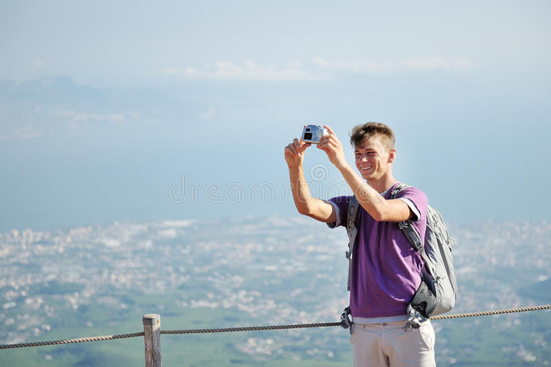 有做照片的背包的年轻远足者在山维苏威,意大利的上面 图库摄影