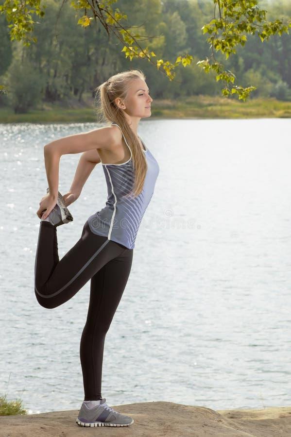 有做运动的身体的美丽的年轻白肤金发的妇女舒展锻炼户外 免版税库存图片