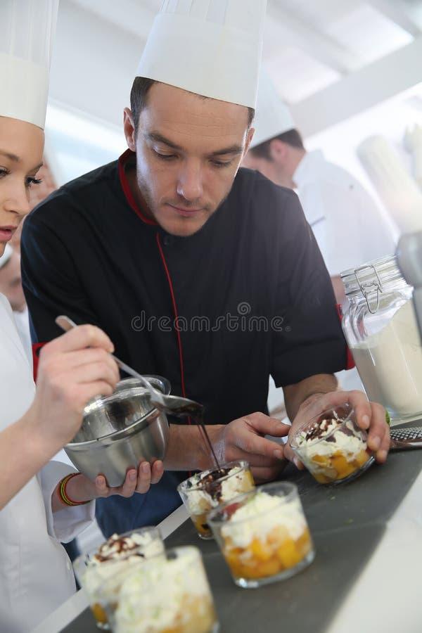 有做酥皮点心的年轻学生的厨师 免版税图库摄影