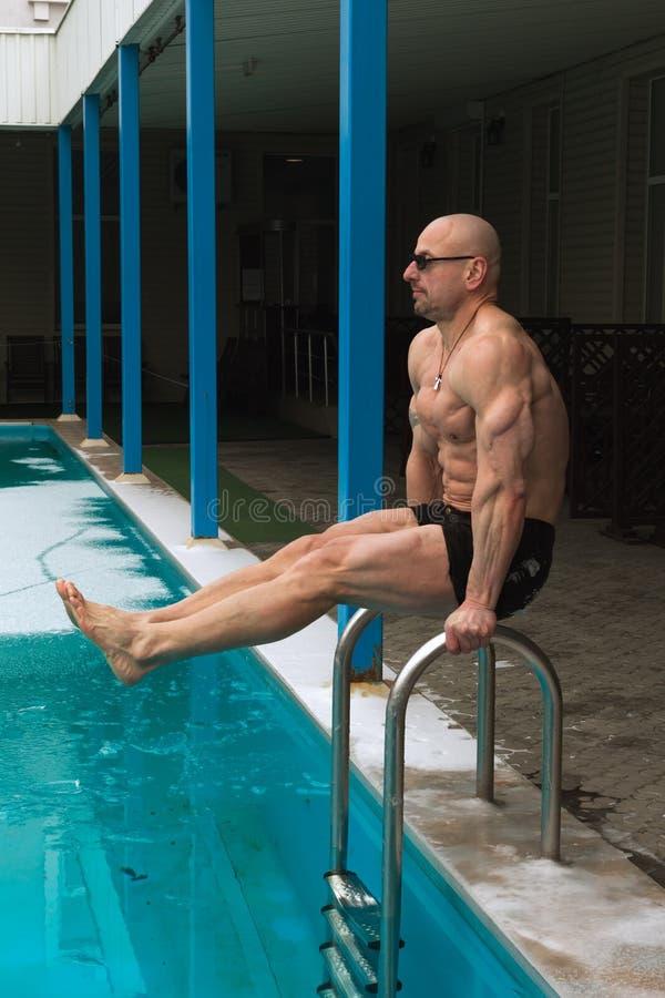 有做锻炼的花格体质的人户外在游泳池附近在冬天 免版税图库摄影