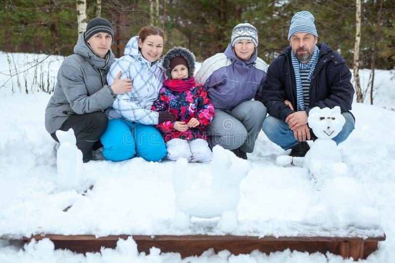 有做雪人,从雪的动物形象的五个人的大家庭 花雪时间冬天 免版税库存照片