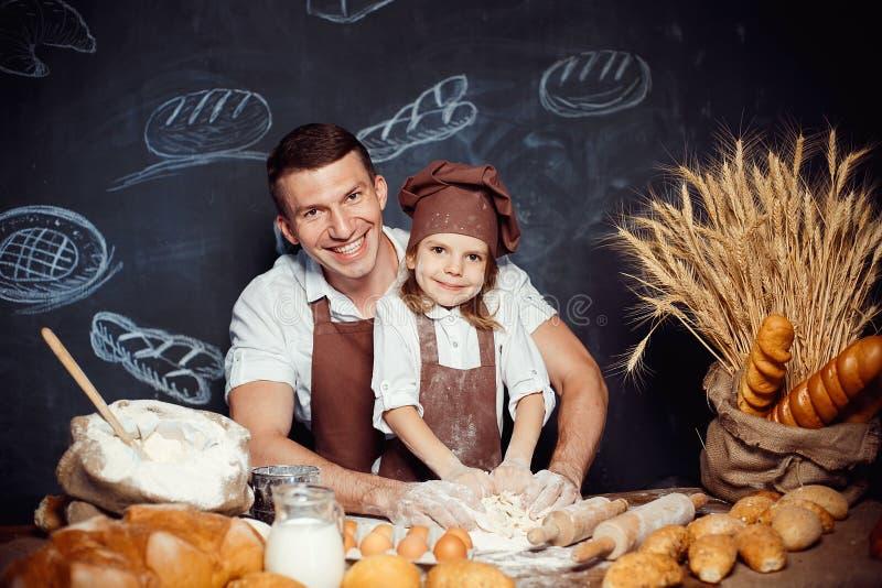 有做面团的父亲的小女孩 免版税库存照片