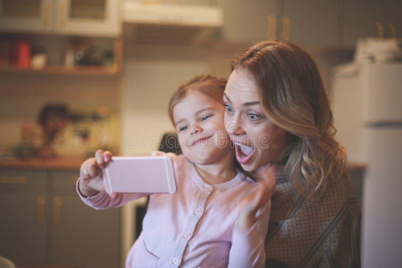 有做滑稽的面孔的女儿的母亲 图库摄影