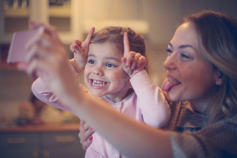 有做滑稽的面孔的女儿的母亲 免版税图库摄影