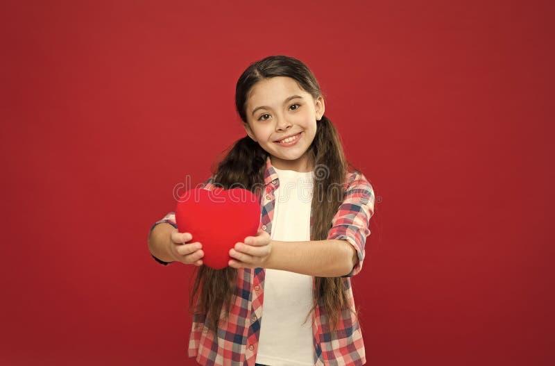 有健康心脏 表现出的小孩爱在情人节 拿着大红心的女孩 逗人喜爱的女孩 免版税库存图片