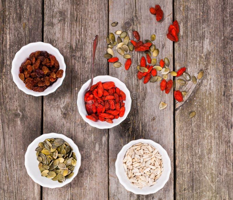 有健康快餐、葡萄干、向日葵种子、南瓜籽仁和狼莓果的四个碗在木背景 库存图片