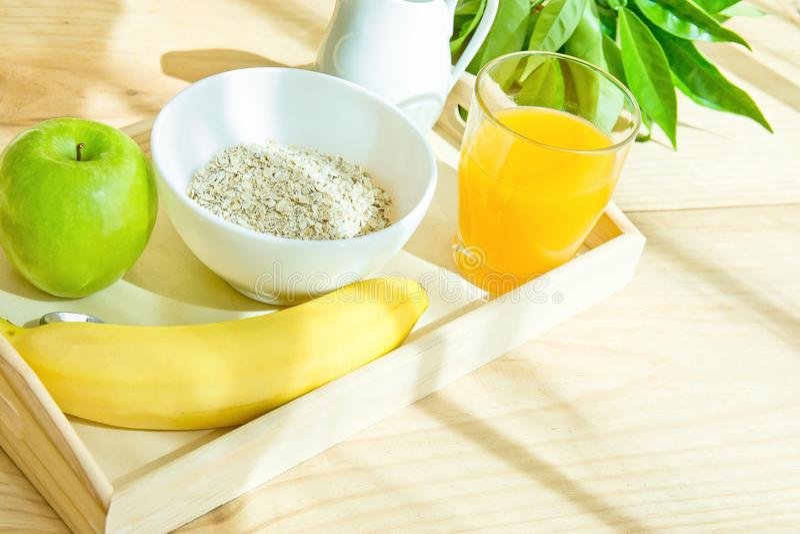 有健康早餐成份的盘子在大阳台的表上 在碗牛奶的燕麦以投手橙汁香蕉绿色苹果计算机 早晨 图库摄影