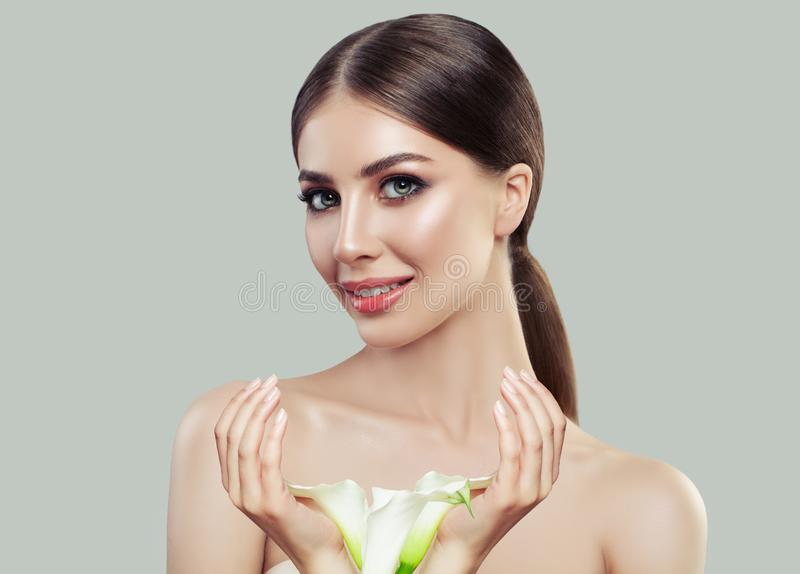 有健康皮肤和白色水芋属的美丽的少妇开花 库存图片