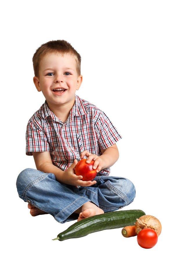 有健康蔬菜和水果的逗人喜爱的微笑的小男孩 库存图片