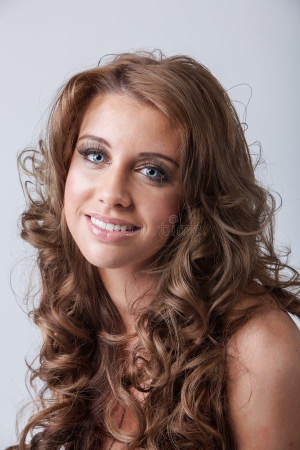 有健康长的卷发的美丽的微笑的妇女 库存照片