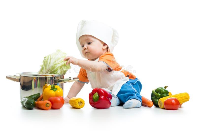 有健康食物菜和平底锅的小厨师 免版税库存图片