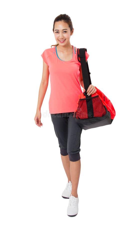 有健身房袋子的亚裔微笑的适合的少妇准备好为健身锻炼的 图库摄影