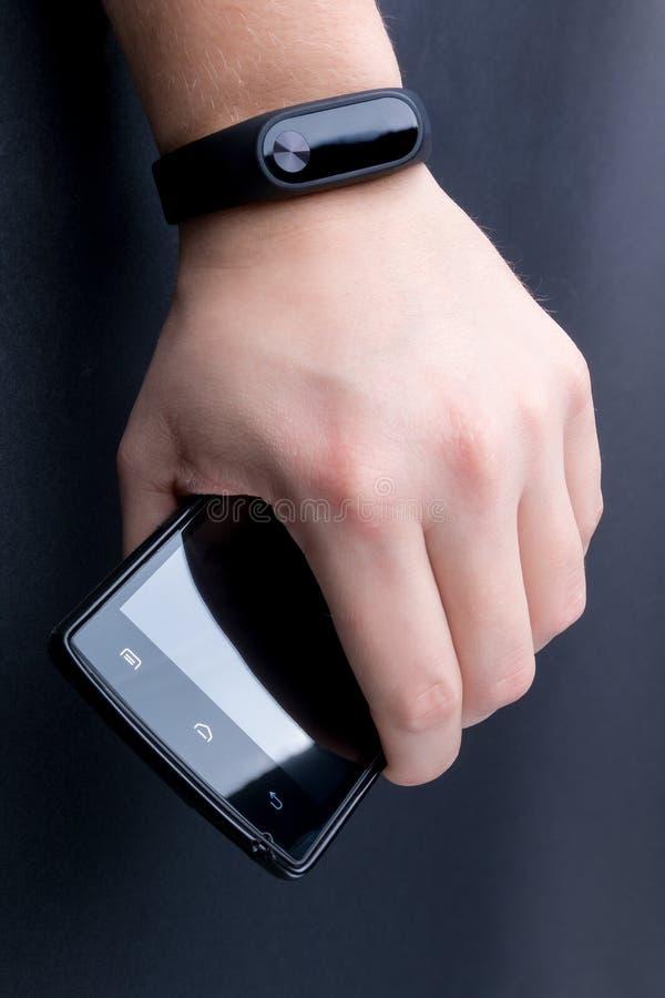 有健身跟踪仪和智能手机的人的手 关闭 免版税库存图片