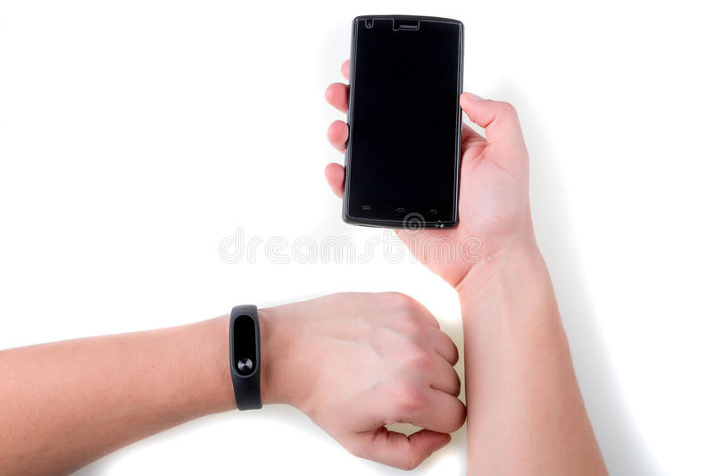 有健身跟踪仪和智能手机的人的手 查出 免版税库存照片