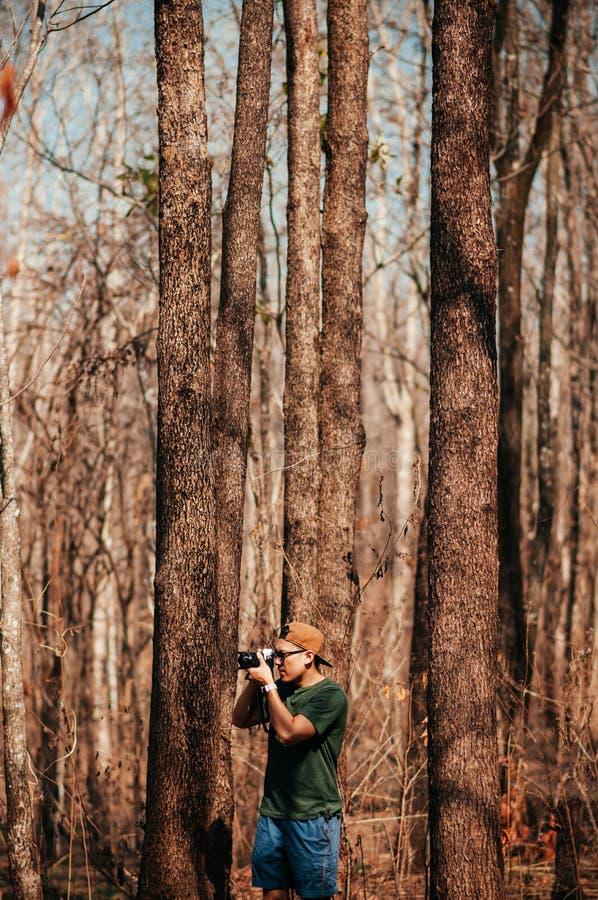有偶然布料的年轻亚裔男性摄影师在森林旅行 免版税库存图片