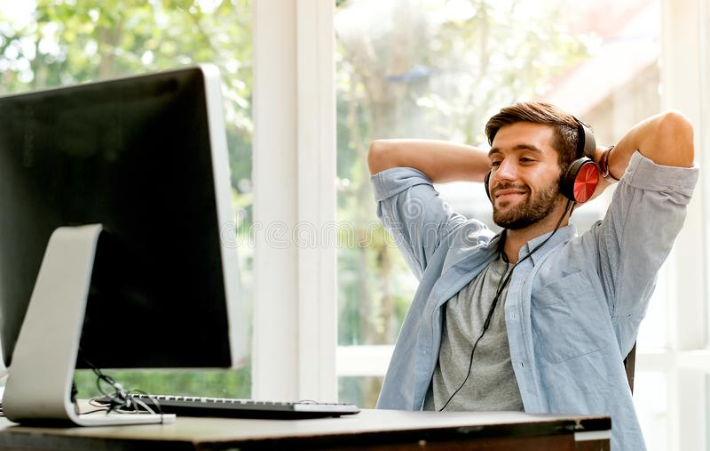有偶然布料的英俊的商人在他的玻璃窗室听着一些音乐从在计算机前面的计算机 免版税库存照片