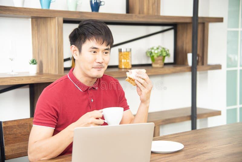有偶然红色T恤杉的亚裔微笑的年轻人喜欢食用早餐,烹调食物和饮料的年轻人在厨房里 图库摄影