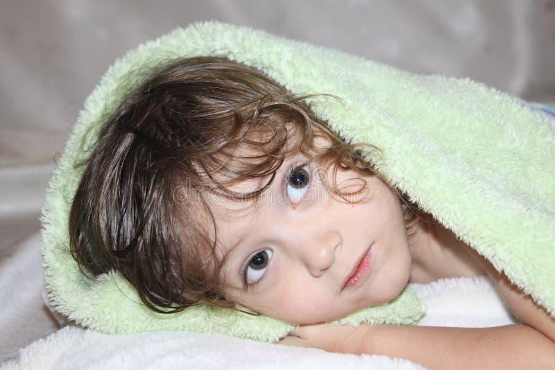 有偷看从地毯下面的卷曲长的金发的可爱宝贝 免版税图库摄影