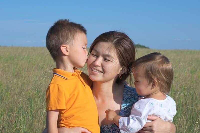 有儿子和女儿的,亲吻妈咪的男孩母亲 免版税库存图片